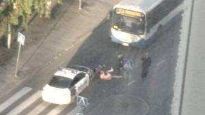 Poliisi ottamassa kiinni alastonta miestä.