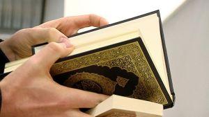 Henkilö selaa Koraania.