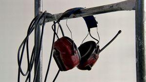 Kuulosuojaimet riippuvat tangossa rakennustyömaalla.
