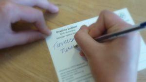 Naisen kädet kirjoittamassa postikorttia