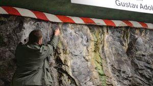 Tutkija tarkastelemassa metroaseman seinää.