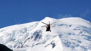 Pelastushelikopteri etsii lumivyöryn uhreja Ranskan Alpeilla 12. heinäkuuta.