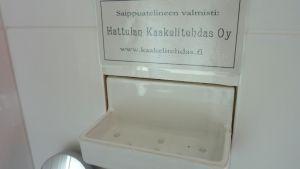 Saippuateline ja kyltti Saippuatelineen valmisti Hattulan Kaakelitehdas Oy