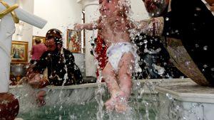 Ortodoksipapit kastavat vauvoja massakastetapahtumassa.