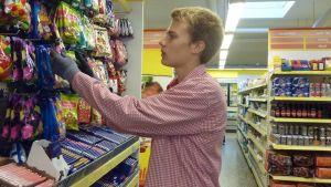 Myyjä täyttää kaupan makeishyllyä