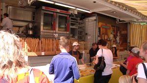 Kokkolalaiset ostamassa patonkeja eurooppalaiselta ruokatorilta.