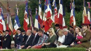 Ihmisiä istumassa muistotilaisuudessa, lippurivistö takana.