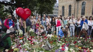 Ihmiset tuovat kukkia pommi- ja ampumatragedian uhrien muistolle.