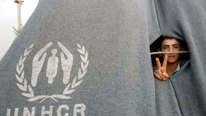 Nuori syyrialainen miespakolainen näyttää voitonmerkkiä harmaan UNCHR:n teltan reiästä.