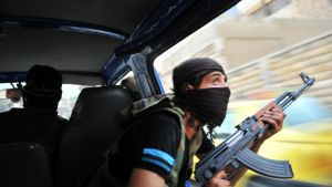 Syyrialaiskapinallinen pitää rynnäkkökivääriä käsissään liikkuvassa pakettiautossa.