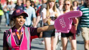 Työntekijä ohjaa ihmisiä olympialaisten avajaisseremonian harjoituksiin 23. heinäkuuta.