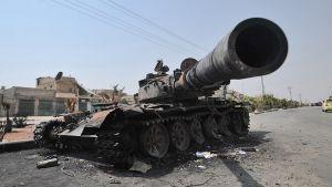 Kapinallisten tuhoama Syyrian hallituksen tankki kadulla.