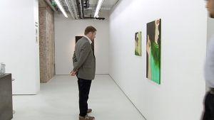 Kulttuuriministeri Paavo Arhinmäki katsomassa taulua galleriassa.