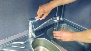 Ihminen laskee vettä hanasta lasiin.