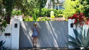 Nuori nainen koettaa nähdä aidan yli talon, josta Marilyn Monroe löydettiin kuolleena 50 vuotta sitten.