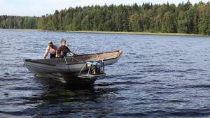 Vanha soutuvene moottoriveneen kyydissä poikittain.