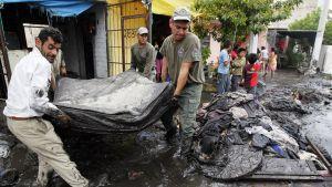 Miehet kantavat kastunutta patjaa mutavellissä kadulla.