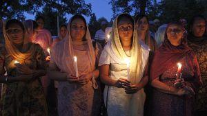 Ihmisiä pitelemässä kynttilöitä muistotilaisuudessa.