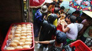 Jakajat jakavat leipää ihmisille sateessa.