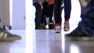 Yläasteikäisiä ja heidän tennareitaan koulun käytävällä.