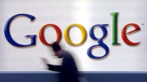 Mies kulkee Googlen seinämainoksen ohi.