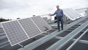 Mies esittelee talon katolla olevia aurinkopaneeleita