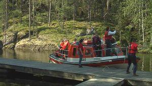 Täynnä ihmisiä oleva järvipelastajien vene rantautuu Etelä-Konnevedellä.
