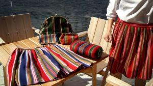 Marianne Valola on suunnitellut kansallispukukankaista muiden muassa laukkuja, sohvatyynyjä, repun ja vyölaukun.