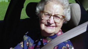 Iäkäs nainen ajaa autoa ja hymyilee.