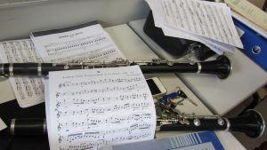 Kuvassa klarinetteja pöydällä ja nuotteja