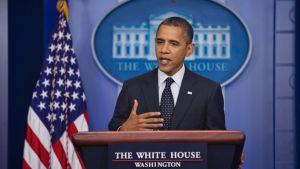 Obama puhujanpöntössä, taustalla Valkoisen talon logo ja Yhdysvaltain lippu.