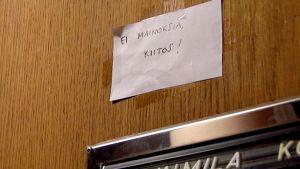 Ei mainoksia kiitos -lappu ovessa.