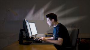 Mies tietokoneen äärellä.