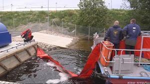 Pelastuslaitos levittää öljypuomia sataman edustalle veneestä käsin.