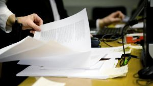 Työntekijä selaa paperipinoa.
