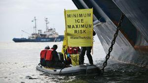 Aktivistit kantavat veneessä kylttiä, jossa lukee Minimum ice - minimum risk.