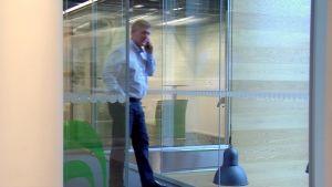 Juha Ropponen puhuu kännykkään lasikäytävällä.