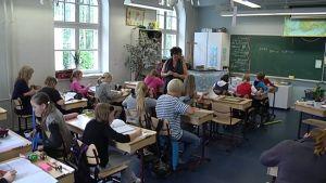 Opettaja ja oppilaita luokkahuoneessa.