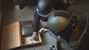 Poliisin ja puolustusvoimien räjähdeasiantuntijat tutkivat vanhaa asesalkkua.