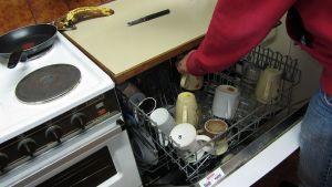 Mies täyttää astianpesukonetta.