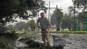 Mies haravoi lehtiä ja oksia Isaacin jäljiltä, joka muuttui hurrikaanista trooppiseksi myrskyksi.