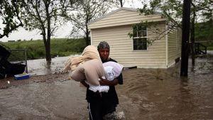 Plaqueminesin alueella asuva Errol Ragas kantaa tavaroitaan turvaan Isaac-myrskyn nostattaman tulvan valtaamasta kodistaan.
