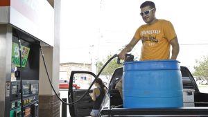Mies tankkaa muoviseen tynnyriin polttoainetta.