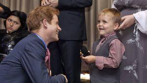 Prinssi Harry ja hymyilee hymyilevälle lapselle.