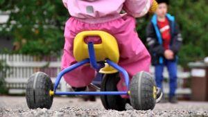Lapsi ajaa leikkimopolla puistossa.