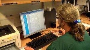 Nainen tietokoneella Keski-Suomen keskussairaalassa