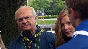 Kuningas Kaarle XVI Kustaa partioasu päällään kuuntelee suomalaisia partiolaisia.