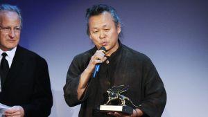 Ki-duk lavalla laulamassa kultainen leijona -patsas kädessään.