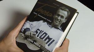 Henkilö pitelee Tapio Rautavaarasta kertovaa kirjaa.