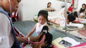 Sairaanhoitaja mittaa denguekuumeeseen sairastuneen lapsen verenpainetta Filippiineillä.